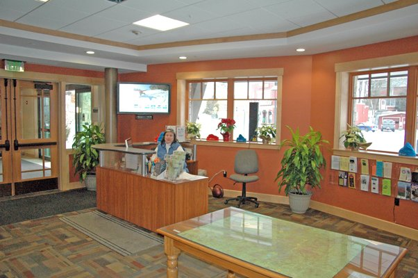 Sharron Miller sits at the front desk of the ROOST/Lake Placid CVB visitors center, located in the Conference Center at Lake Placid.