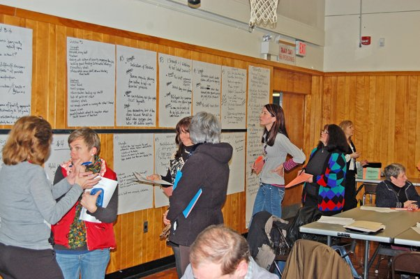Participants and school board members read the thoughts and ideas posted on the wall of those who gathered for Plattsburgh City School's Stakeholders' Roundtable Budget Forum.