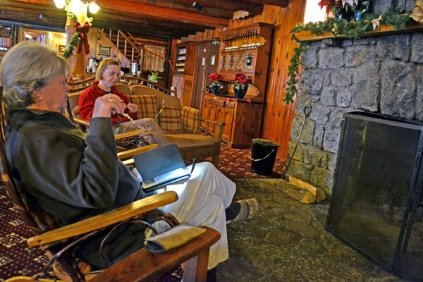 Long-time visitors to Garnet Hill Lodge relax by the fire in the main room. RoseAnn Fogarty knits while chatting about Kathy Silo's Kindle reading.