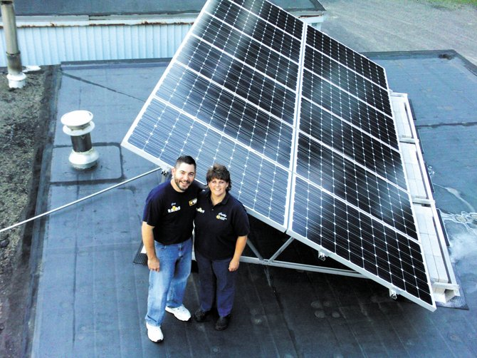 Hudson & Mowins owners Greg and Cathy Hudson stand by the solar panels on the business' rooftop.