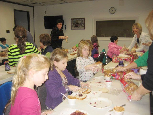 Allison Hay, left, Mollie Fabian, center, and Audrey Benton, members of Baldwinsville's Brownie Troop 10319, make sandwiches to donate and deliver to the Samaritan Center in Syracuse.