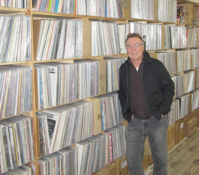 Jack Wolak, owner of Rare Necessities in Mattydale, stands with some of his many albums he ships out around the world. Sales for the vinyl record industry have jumped over 36 percent over last year.