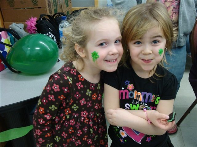 Four-year-olds Kendra Stock, left, and Hannah George show off their shamrock painted faces while enjoying mint-green Oreo cookies during PEACE, Inc. County West Family Resource Center's St. Patrick's Day event held March 14 with the help of Baker High School's Key Club.