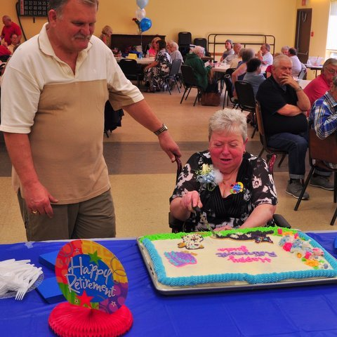 Jude Laurange cuts the first slice of her retirement cake with her husband, George, at her side.
