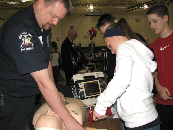 Matt Cheevers, a paramedic with the Greater Baldwinsville Ambulance Corps, assists a student testing a medical device. On March 29, Ray Middle School held its second annual career fair for its seventh-grade students.