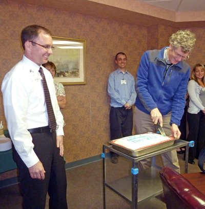 Dr. Glen Chapman, right, cuts a cake presented to physicians in honor of Doctor's Day. Dr. Chapman has served Inter-Lakes Health for over 27 years. Left is Chip Holmes, CEO of Inter-Lakes Health.