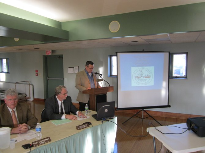 Mayor Mark Atkinson (standing) presents this year's village of North Syracuse budget during a public hearing at the village community center April 12 as Trustee Gary Butterfield (left) and Deputy Mayor Chuck Henry look on.