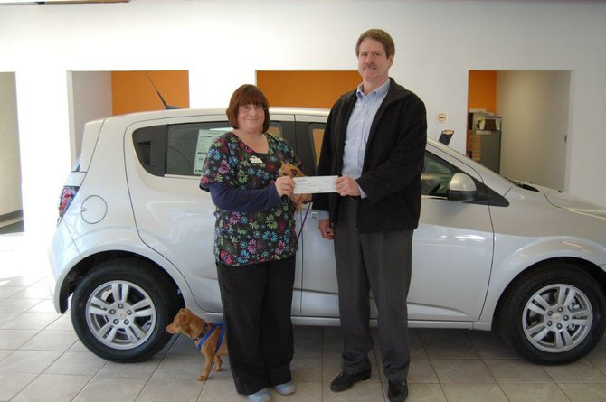 "Dee Schaefer of Wanderer's Rest animal rescue organization, along with four-legged friends Jasmine (in her arms) and Rodney, accepts a $250 donation from Mark Evans, president of Evans Chevrolet in Baldwinsville. The donation was based on Evans Chevrolet gaining additional ""likes"" on its Facebook page."
