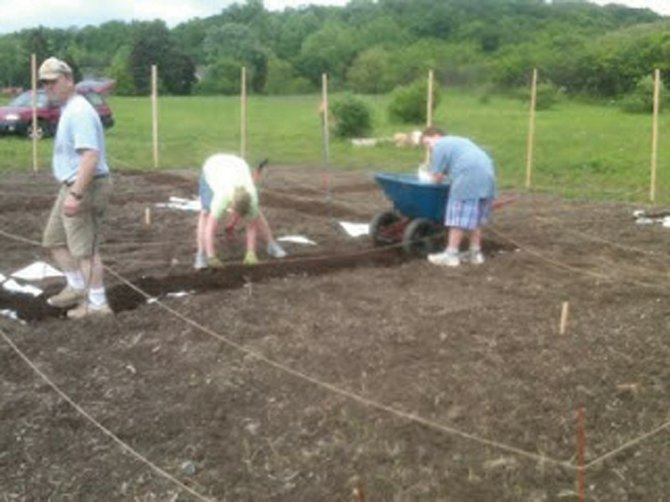 Community members work in the Community Growth Project gardens in Camillus last year. This spring and summer, the Cafe @ 407 in Liverpool will also have a plot in the garden.