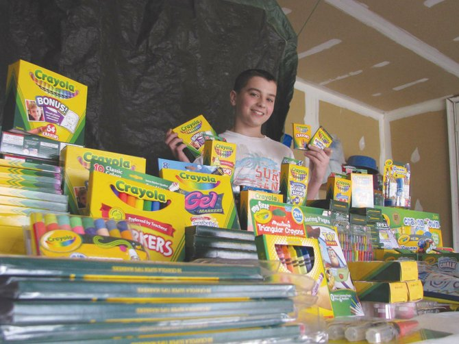 Ryan Gilbert, 13, of Clay, poses with the 321 boxes of Crayola products he's collected to donate to the Upstate Golisano Children's Hospital in Syracuse. Gilbert collected the crayons in memory of his cousin, Bianca Bresadola, who passed away at age 7 after a battle with osteosarcoma in December of 2008.