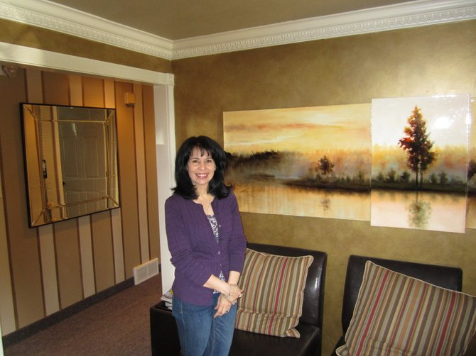 Bonnie Marini, owner of the salon and spa Shear Perfection, stands in her business's reception room. The local school psychologist runs Shear Pleasure as her second job. Including Marini, the new business employs nine people.