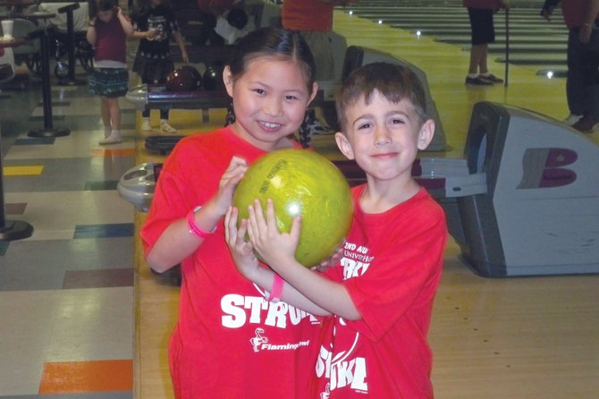 Two young participants take part in last year's Strikes Against Stroke fundraiser at Flamingo Bowl in Liverpool. The event raises money for the Upstate Stroke Center at Upstate Medical University.