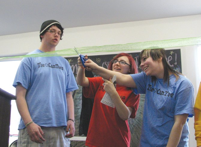 Breanna Goldthwait, center, and Melissa Mizzouli cut the ceremonial ribbon at Sunday's grand opening of the CanTeen's new home at 6046 Route 31, next to Cicero-North Syracuse High School. Watching is Josh Heffernan. All are CanTeen participants.