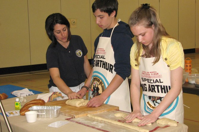 Gina Ciancia, left, a representative with the King Arthur Flour Company, directs Ray Middle School student Nicholas Boulton as he kneads bread dough while his classmate Kathleen Thayer works on creating a loaf of braided bread during an assembly.