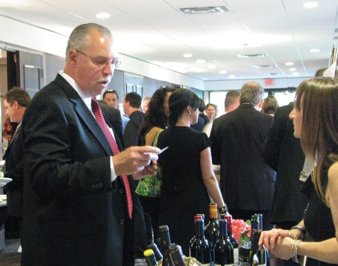Cicero Police Chief Joseph Snell samples some of the wine available at the North Area Meals on Wheels annual Spring Gala Friday night at the Doubletree Hotel in East Syracuse.