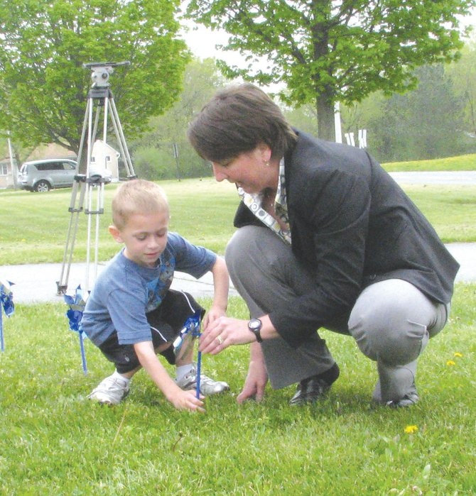 McMahon/Ryan Child Advocacy Center Executive Director Julie Cecile, right, helps CHE kindergartener Aiden Bovenzi plant a pinwheel in the school's front lawn. The school planted 400 pinwheels after raising $400 for McMahon/Ryan.