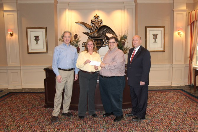 Anheuser-Busch General Manager Steve McCormick, left, and Debra Dunham, Anheuser-Busch Packaging Materials Quality Manger and United Way Campaign Coordinator, present a $50,000 corporate gift check to United Way of Central New York President, Frank Lazarski, second from right, and Account Manager, Tim Ferlito, right.