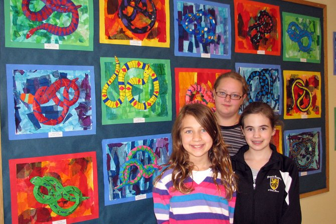 Fifth-graders Emily Evans, back, Leah Carpenter, left, and Faith Scheemaker stand in front of a display of fifth-grade artwork at McNamara Elementary School.