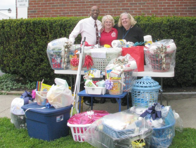 From left, Rembert Lane, executive director of the Peter Young Veterans Housing program on Gifford Street in Syracuse, Alice Bigelow of the American Legion Ladies Auxiliary Unit 188 and Veterans Administration Medical Center social worker Mary Driscoll pose with the baskets collected by other American Legion auxiliaries for the veterans' home.