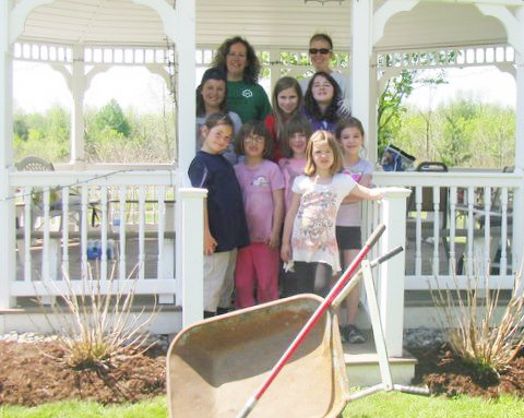 Girl Scouts from Troop 10134 (pictured) recently spent a spring Saturday at Canton Woods Senior Center weeding the flower bed around the center's gazebo and planting beautiful flowers for the seniors to enjoy throughout the summer season.