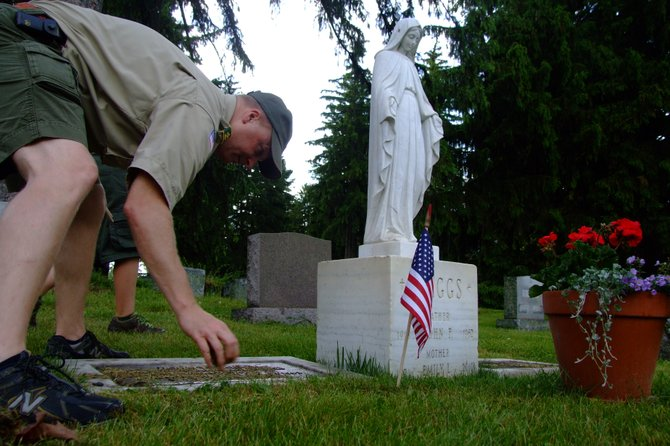 Assistant Scoutmaster Michael DuBois removes debris from a veteran's grave.