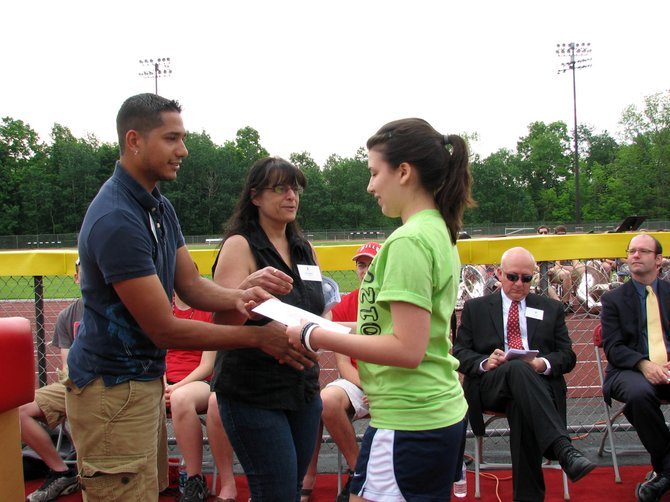 Jose Castro, Jr. and Debbie Castro present Jessica Futrell with the Anthony Castro Memorial Scholarship at Baker High School's Annual Moving Up Day ceremony on May 25.