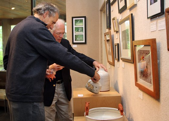 "Larry Master and Peter Galvani admire artwork at ""Artists for Animals"" exhibit."