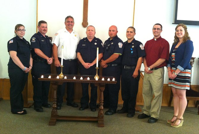 (From left) Alex Grigg, Billy Crowder, Mark Harrison, Rick Curtis, Drew Gilbert, Stephen Curtis, Rev. Gary Rarick and Christie O'Brien (representing Congresswoman Anne Marie Buerkle) hold lit candles in recognition of a Memorial Day celebration in Plainville honoring volunteer firefighters.