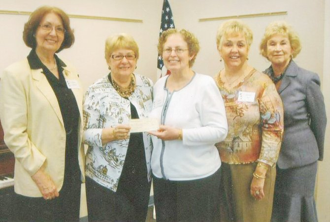 Baldwinsville Public Library Director Marilyn Laubacher, center, accepts a check from Millie Sauter, treasurer of the Travelers Club of Baldwinsville.