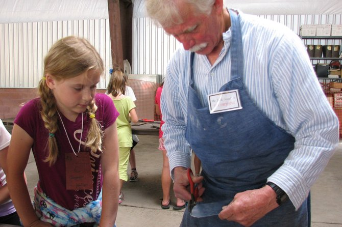 At the Baldwinsville Central School District's Colonial Festival, volunteer Jack Gramlich shows fourth-grader Summer McClintic how he cuts tin.