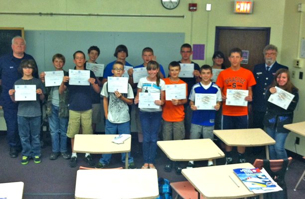 Ticonderoga students who successfully completed the Coast Guard boating safety course pose with instructors William Doyle and Commander Eugene Frost.