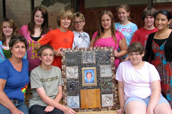 Displaying the memorial they created for their friend Wayne Dogdge are Ray Middle School students (back row, from left) Jody Allen, Miranda Clark, Tyler Bausch, Paul Schmid, Amanda Byrns, Destiny Gardner, James Coomey, school social worker Jill Joseph (front row, from left) art teacher Debra Lynch, Jacob Bardenett and Gabrielle Sellin. Missing is Maia Falise.