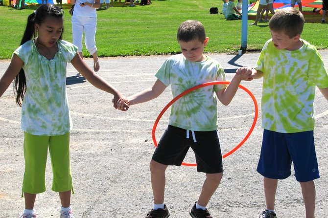Skye Margiotta, left, and her classmate Rory Mastine, right, aren't sure if Joseph Natale can get the hoop over his body without touching it with his hands during an activity at Palmer Elementary School's Summer Olympics.
