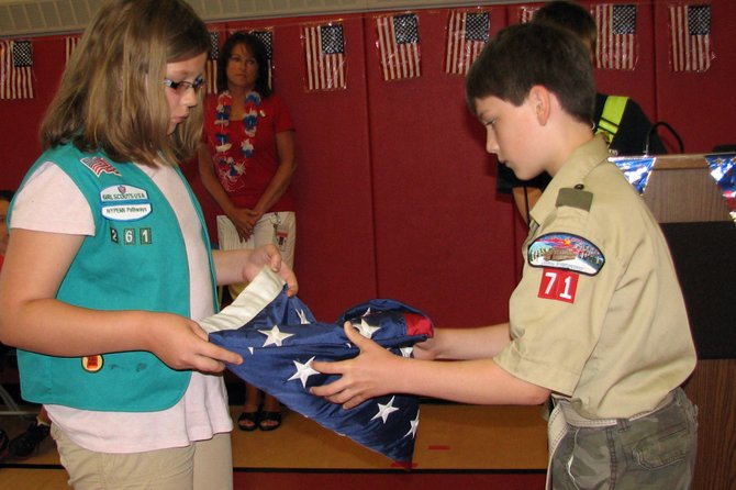Makayla Schanz, left, and Aaron Sprague fold up the American flag during Elden Elementary School's Flag Day ceremony, held June 14.