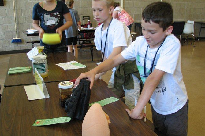 Sixth-grader Brandon Steuer checks out a model of a lung damaged from smoking as his classmate Cody Neish looks on during Ray Middle Schools wellness fair. Held for sixth- and seventh-graders, the fair showcased good nutrition and exercise as part of a healthy lifestyle. Students rotated through activities inside and outside including aerobics, rowing, nutrition education and sampling healthy foods.