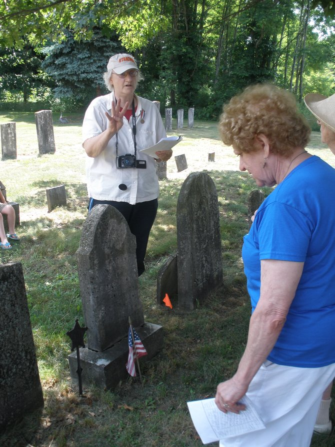 Sue Greenhagen, left, describes the Civil War-era grave markers at Pine Plains Cemetery in Clay during the cemetery's bicentennial celebration while town historian Dorothy Heller listens.