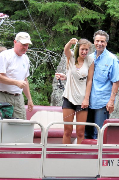 NYS Governor Andrew Cuomo admires his daughter's catch,  while fishing on the Saranac Lakes.  The Governor recently signed legislation that will permit the DEC to host additional Free Fishing Clinics throughout the state.  It is expected the introductory clinics will attract newcomers to the sport,  and generate additional licenses, fishing equipment sales and additional expenditures