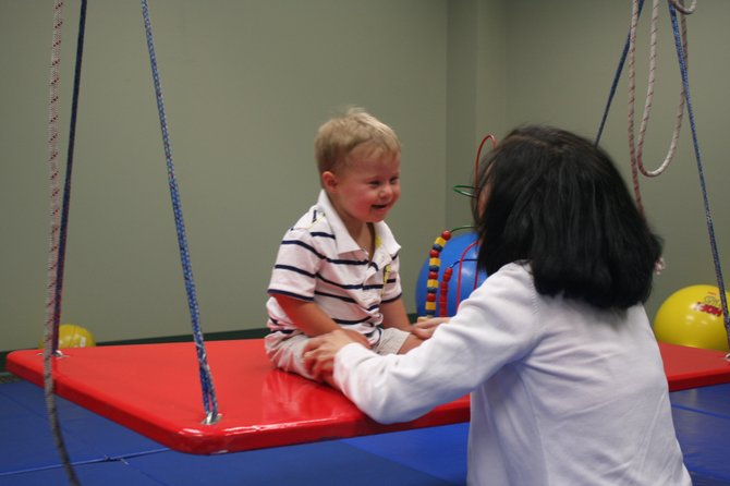 Physical therapist Anne Marie Abt gets a smile from Adam during his therapy session.