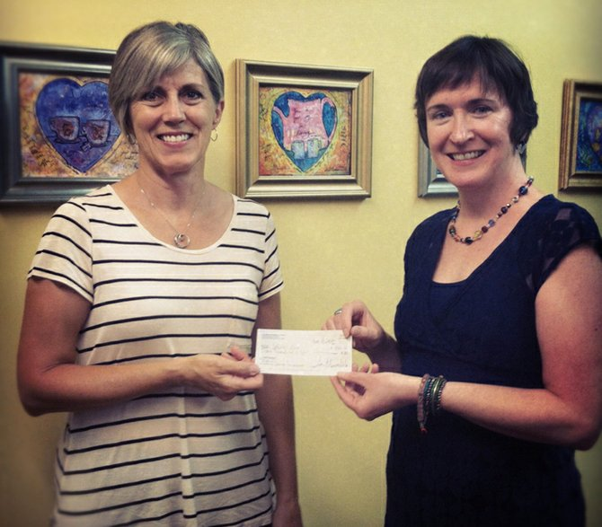 Clare Murray Volo, right, presents Jodie Wilson-Dougherty, executive director of Ophelia's Place, with a $500 donation to Ophelia's Place.