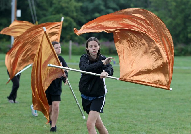 Signs that summer break is quickly coming to a close – the Baldwinsville Marching Band and varsity football team began practicing for their upcoming seasons Monday, Aug. 13, at Baker High School. Lydia DiCaprio twirls a color guard flag during marching band practice.