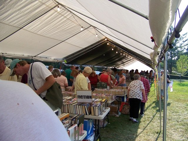 Shoppers enjoy browsing the many tables and titles of used books under the tents in McHarrie Park during the Museum at the Shacksboro Schoolhouse's annual book sale.  This year's 22nd annual event will be held Sept. 6 to 10.