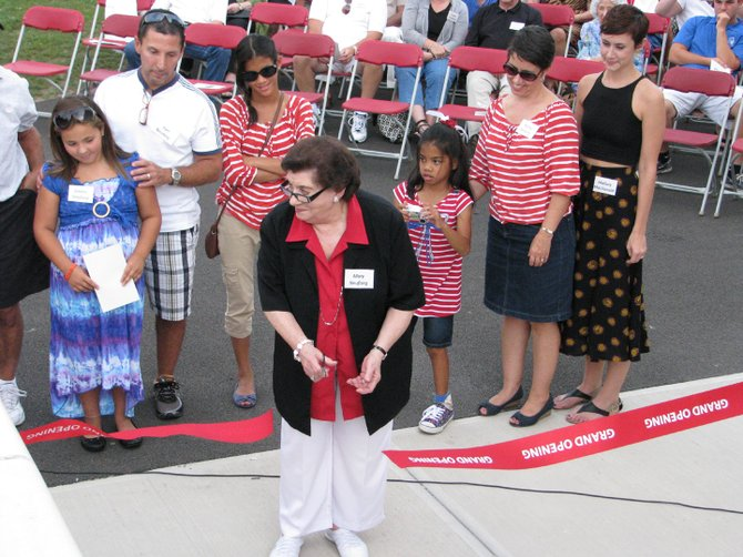 Mary Neufang cuts the ribbon during a dedication of the Bill Neufang Facility at Pelcher-Arcaro Stadium on the main campus of the Baldwinsville Central School District. Bill Neufang, a teacher and coach in the district for more than 30 years, passed away in June 2011. More than 100 people enjoyed the Sept. 7 dedication of the concessions facility.