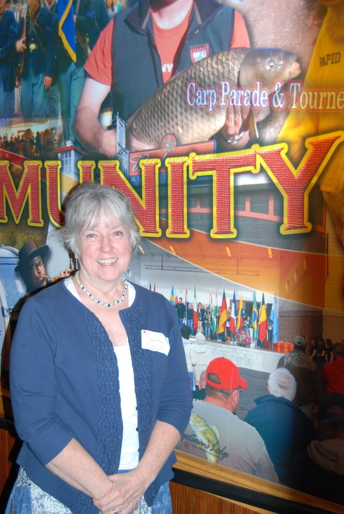 Marianne Miles stands with a collage at Applebees on Route 31 made from photos she has taken in and around Baldwinsville.