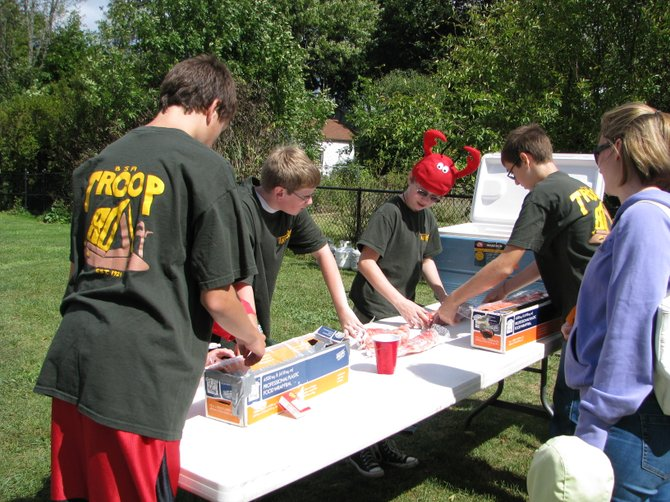 Boy Scouts from Troop 80 work together efficiently to wrap steamed lobsters as quickly as they can for people waiting in line. The boys had more than 1,000 crustaceans ready to hit the steamers set up Sept. 15 at Mercer Park.