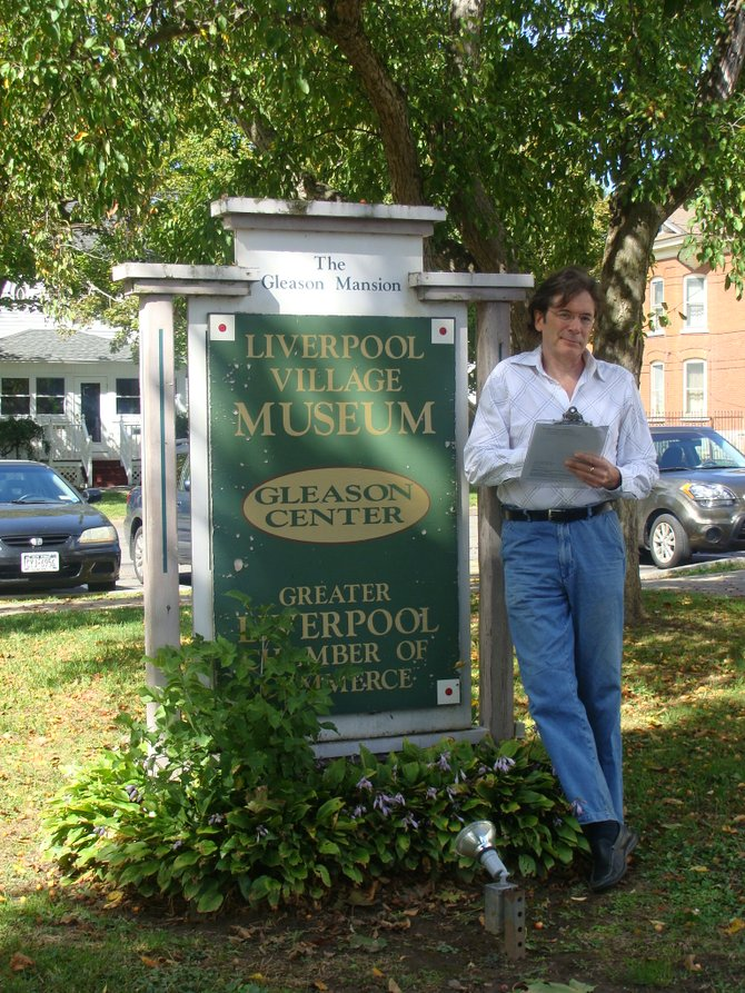 Onondaga Historical Association Educational Coordinator Scott Peal looks over his notes on the scripts for  performers in this month's Ghostwalk, taking place in the Village of Liverpool.  Peal stands beside the sign marking the Gleason Mansion, located on the corner of Sycamore and Second Streets.  The former home of Lucius Gleason now houses the Village Museum, Chamber of Commerce, and offices, and is situated between the Liverpool Village Hall - Police Department on one side and the Willow Museum on the other.  The mansion is one of several stops along the Ghostwalk.