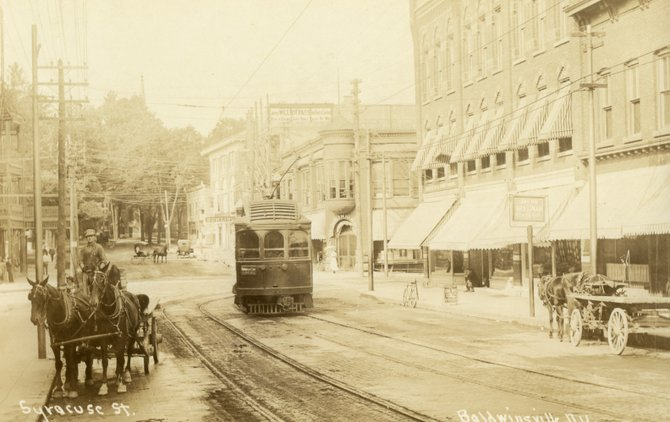 "This photo postcard of a trolley rounding the Four Corners in the center of Baldwinsville 100 years ago, is featured on the front cover of Bob Bitz's newest local history book, ""Transportation in Central New York and the Baldwinsville Area 1600 to 1940."" Bitz will discuss his books and be available for signing on Sunday, Oct. 7, at Baldwinsville's Museum at the Shacksboro Schoolhouse."