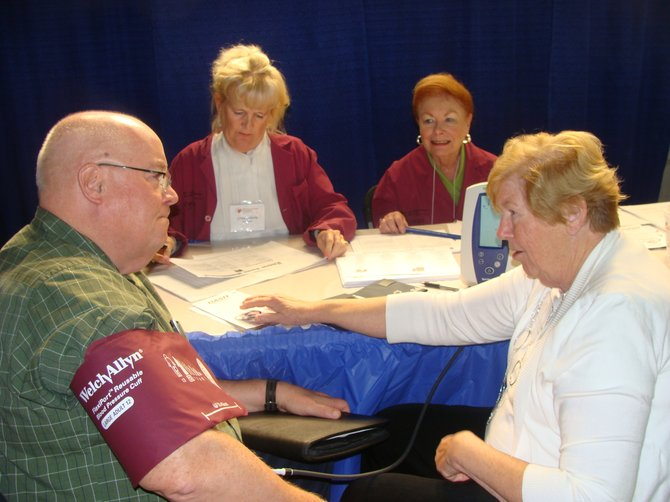 "Mary Kay Gillis, RN, MS and director of clinical programs for the National Kidney Foundation of Central New York, seated at right, takes the blood pressure of  John M. Ferguson of Minoa Thursday during the eighth annual Senior Fair, organized by State Sen. John A. DeFrancisco. Many volunteers were on hand to take the blood pressures of attendees, sponsored by the National Kidney Foundation. Gillis, who is retired Sept. 28 after 57 years in nursing, said ""This is what I love  best about the fair, the one-on-one interaction with people."" She lives on Otisco Lake and has done volunteer work for the Kidney Foundation since 2000."