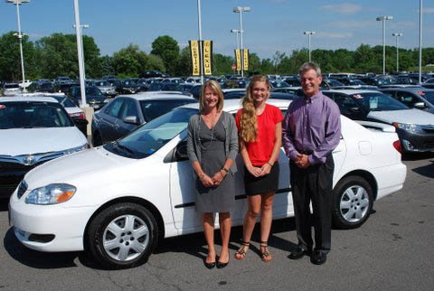 Andrea Moore (center), Baker High School's Keep the Ball Rolling 2012 grand prize winner, stands with her 2005 Toyota Corolla prize, which was generously donated by Burdick Automotive BMW, Ford, Lexus and Toyota-Scion. With her are Kelly Pelcher, left, and Kevin Burdick.