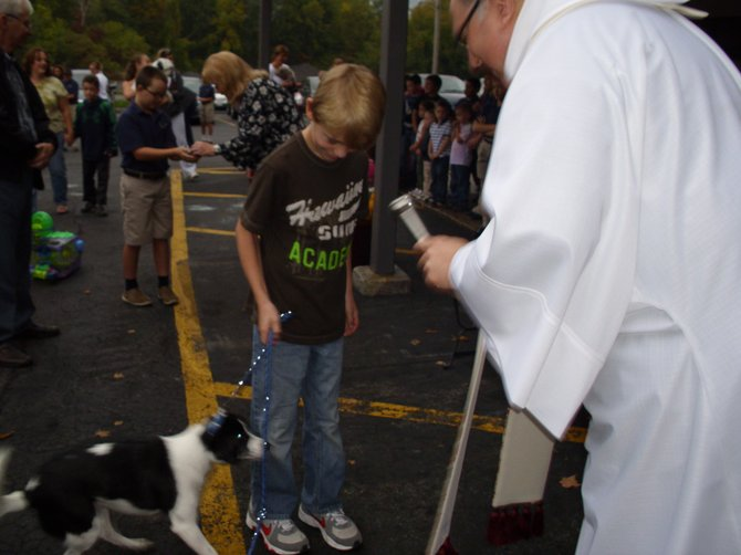 Father Joseph Scardella, right, blesses Casey Burke's dog Bailey during the Feast of St. Francis held Oct. 4 at St. Mary's Academy in Baldwinsville.