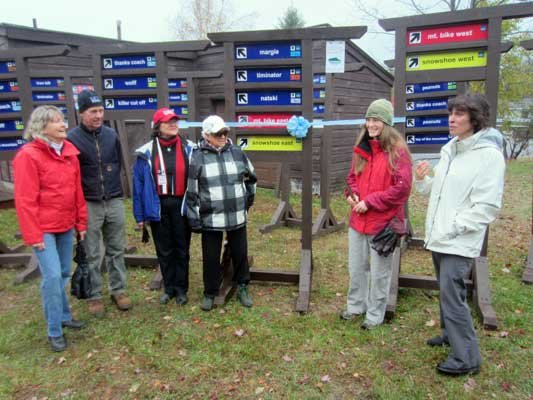 Honorees Mary Jean Burke, Jack Burke, Helen Demong and Natalie Leduc listen as Jamie Konkoski and Margot Gold of North Country Healthy Heart Network prepare to cut the ribbon on new cross-country-ski trail signs at Dewey Mountain Recreation Center in Saranac Lake Sunday.